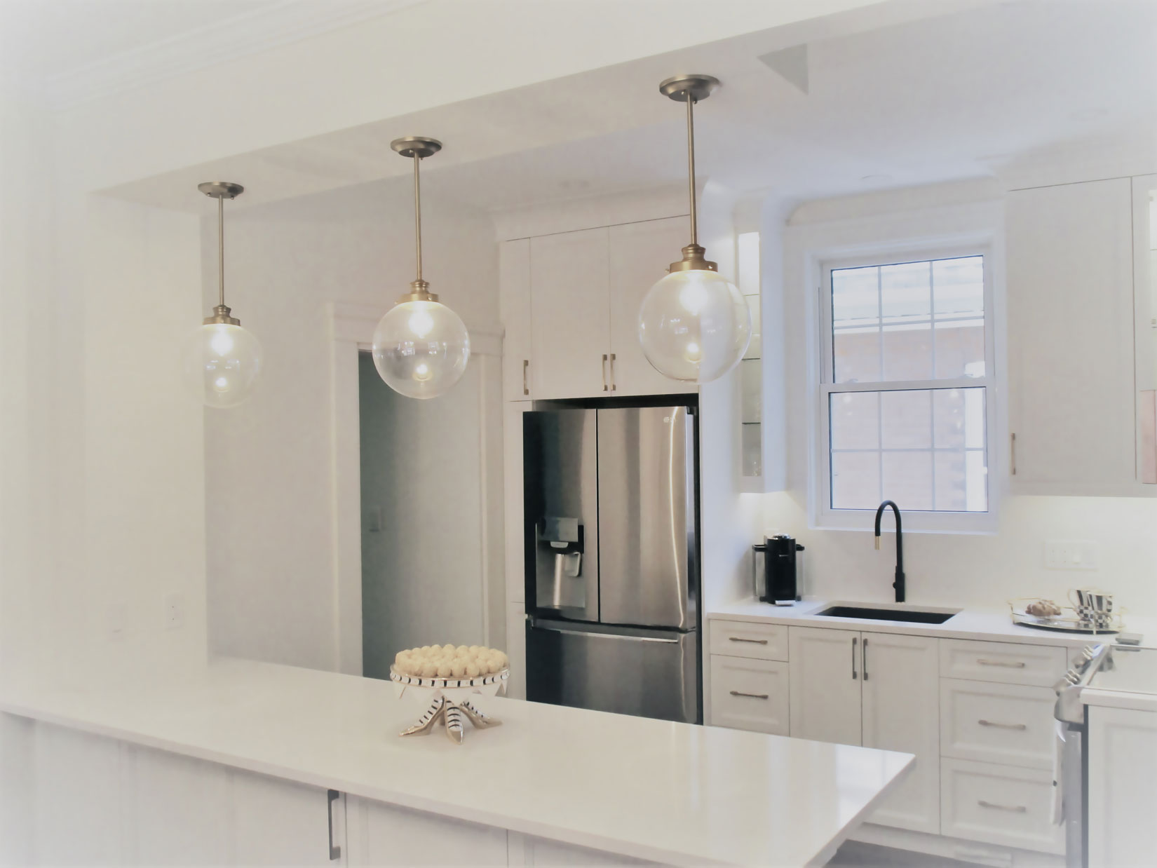 MDF Maui doors in Simply White. Quartz countertops. Contemporary pulls in gold.
